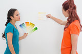 Two female friends choosing color for painting a room