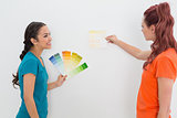 Two happy female friends choosing color for painting a room