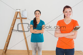 Friends with paint brushes and ladder in a new house