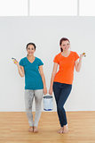 Smiling female friends with brushes and paint can in new house
