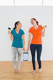 Cheerful friends with brushes and paint can in new house