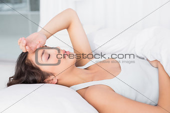 Sleepy young woman suffering from headache with eyes closed in bed