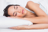 Pretty young woman sleeping with eyes closed in bed
