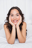 Close-up of a smiling brunette lying in bed