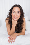 Portrait of a smiling brunette lying in bed