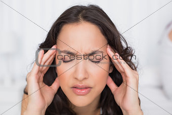 Beautiful woman suffering from headache with eyes closed