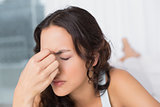 Woman suffering from headache with eyes closed at home