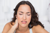 Woman suffering from neck pain with eyes closed