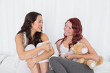 Relaxed female friends chatting over coffee in bed