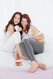 Happy young female friends with coffee cups in bed