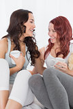 Cheerful female friends chatting over coffee in bed