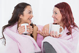 Female friends with coffee cups in bed