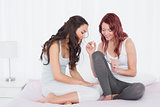 Pretty young woman painting friends nails on bed