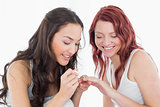 Pretty young woman painting a smiling friends nails
