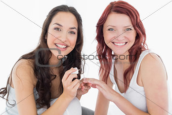 Smiling pretty young woman painting friends nails