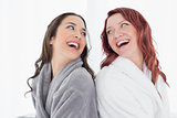 Happy female friends in bathrobes standing back to back