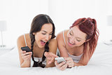Cheerful young female friends text messaging on bed
