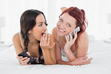 Shocked woman looking at a cheerful friend while on call in  bed