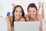 Relaxed female friends doing online shopping in bed