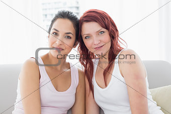 Portrait of two beautiful young female friends at home