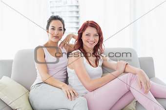 Two beautiful young female friends in living room