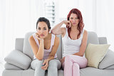 Unhappy female friends not talking after argument on couch