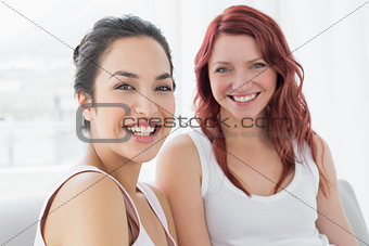 Portrait of two beautiful young female friends smiling