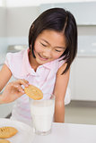Smiling girl enjoying cookies and milk at home