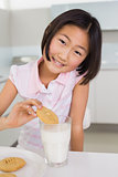 Portrait of a smiling girl enjoying cookies and milk