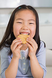 Portrait of a smiling young girl enjoying cookies