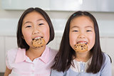 Portrait of two smiling young girls enjoying cookies