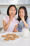 Two smiling girls enjoying cookies and milk in kitchen