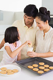 Girl enjoying cookies and milk with parents in kitchen