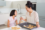 Girl looking at her mother prepare cookies in kitchen