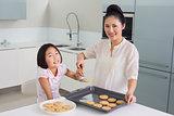 Girl helping her mother prepare cookies in kitchen