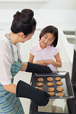 Girl helping her mother prepare cookies in kitchen