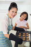 Portrait of girl helping her mother prepare cookies in kitchen