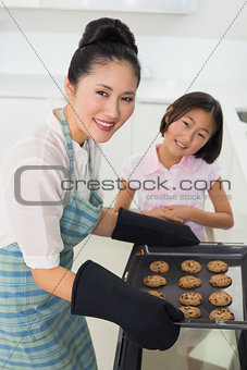 Portrait of girl helping her mother prepare cookies in kitchen
