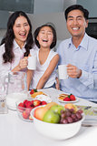 Cheerful young girl enjoying breakfast with parents