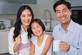 Happy young girl enjoying breakfast with parents