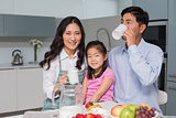 Portrait of a happy young girl enjoying breakfast with parents
