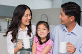 Portrait of a young girl enjoying breakfast with parents