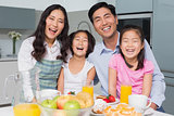 Cheerful family of four enjoying healthy breakfast in kitchen