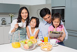 Family of four enjoying healthy breakfast in kitchen