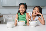 Two smiling young girls sitting with bowls in kitchen