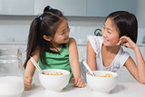 Two smiling young girls sitting with cereal bowls in kitchen