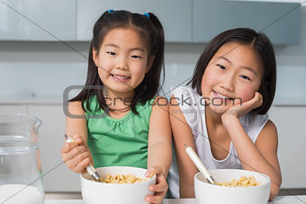 Portrait of two smiling girls sitting with bowls in kitchen