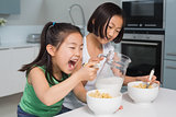 Two happy young girls eating cereals in kitchen