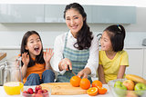 Woman with cheerful two daughters cutting fruit in kitchen
