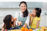 Woman with happy two daughters cutting fruit in kitchen
